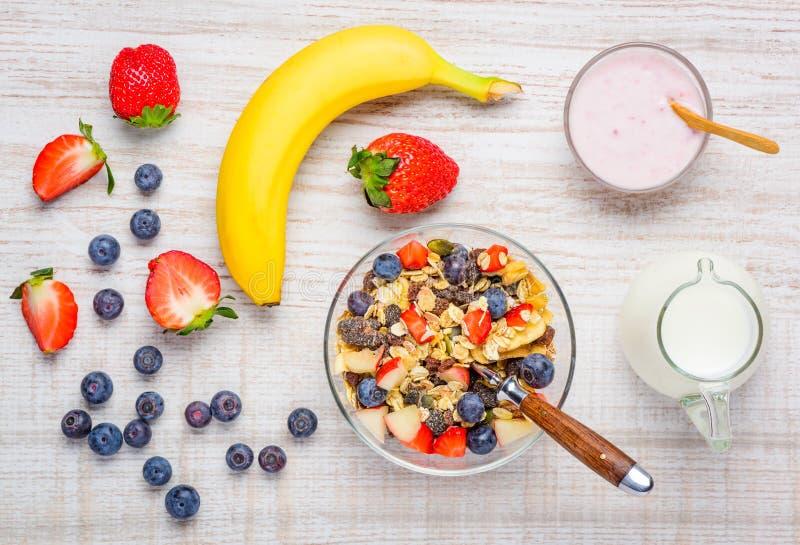 Den sunda myslit frukosterar med ny organisk frukter och yoghurt royaltyfria foton
