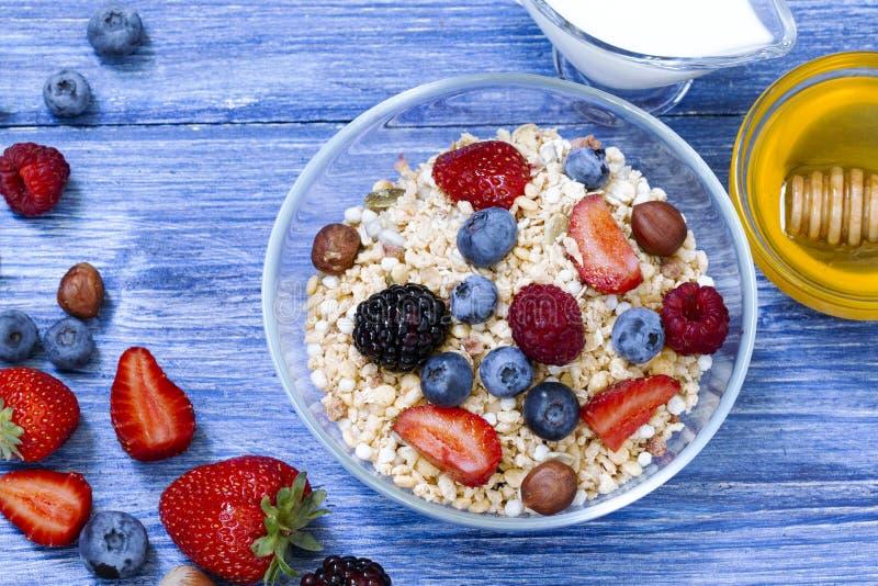 Den sunda myslit med hallonet, blåbäret, jordgubben, Blackberry, hasselnöt, mjölkar och honung på den blåa trälantliga tabellen royaltyfria foton