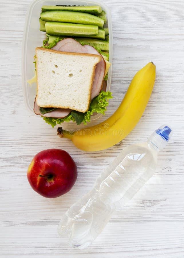 Den sunda skolalunchasken med nya organiska grönsaker skjuter in, frukter och flaskan av vatten på den vita trätabellen, över huv arkivfoto