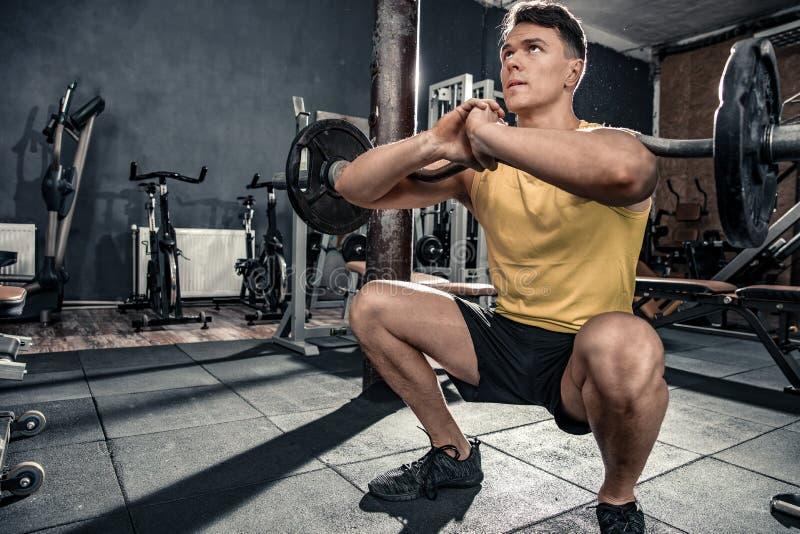 Den sunda unga mannen med krullningsstången utför squats royaltyfri bild