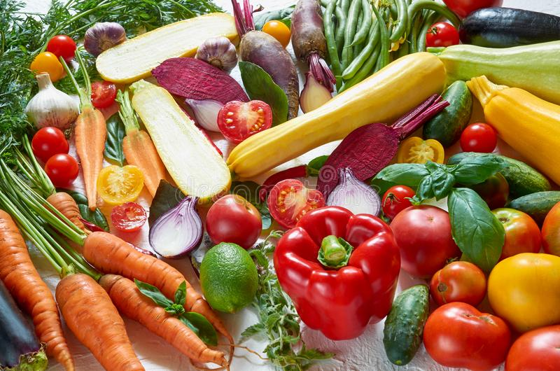 Den sunda vegetarian bantar matbakgrund Olika nya organiska grönsaker på den vita tabellen: tomater skivad zucchini, beta royaltyfria foton