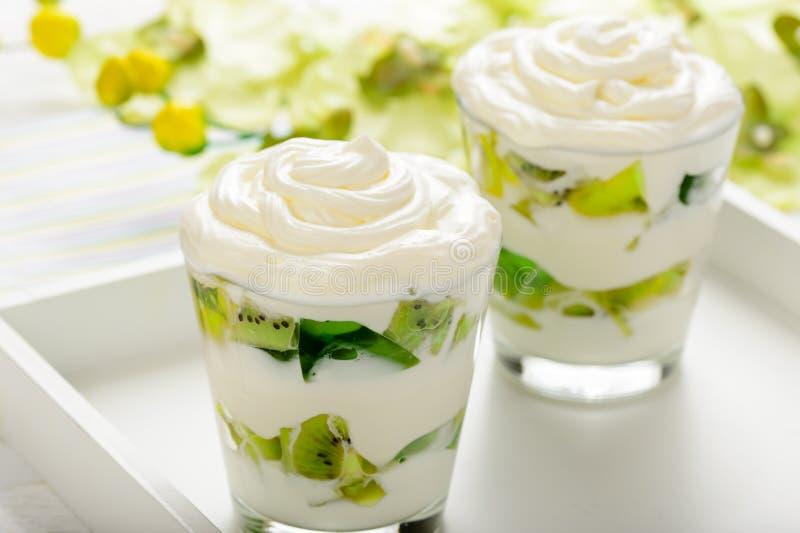 Den sunda yoghurtefterrätten med kiwi, stelnar och lagar mat med grädde i exponeringsglas arkivbild