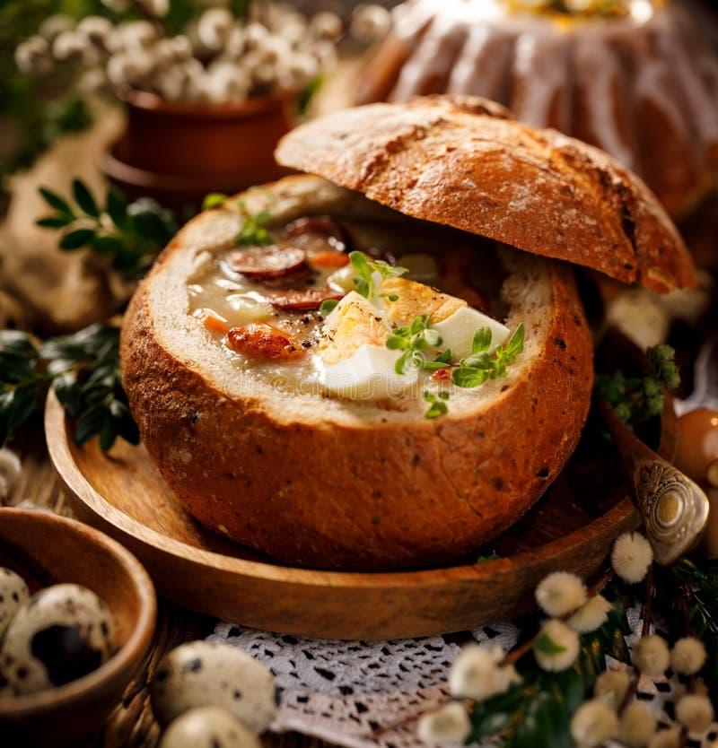 Den sura soppan som gjordes av rågmjöl med korven och ägg, tjänade som i brödbunke Traditionell easter polsk sur rågsoppa royaltyfri fotografi