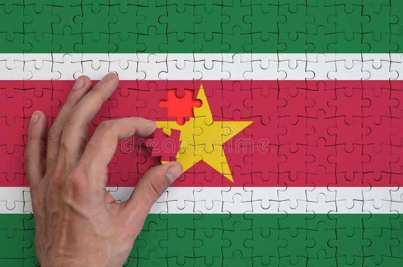 Den Surinam flaggan visas på ett pussel, som handen för man` s avslutar för att vika fotografering för bildbyråer