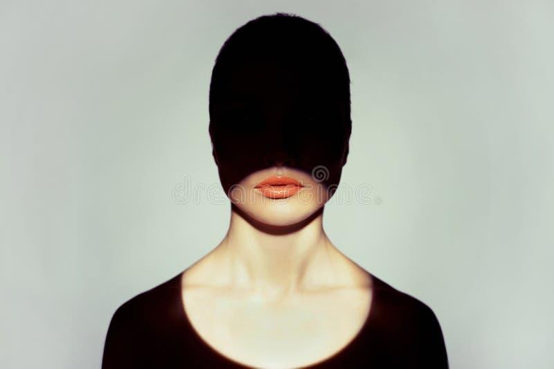 Den Surrealistic unga ladyen med skuggar på henne förkroppsligar arkivfoto