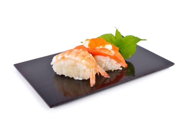 Den sushinigirien och sashimien tj?nade som p? den plana svarta plattan med vit bakgrund arkivfoton