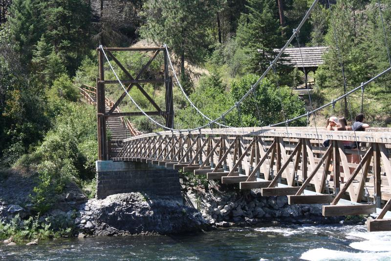 Den svängande bron på flodstranden parkerar arkivbild