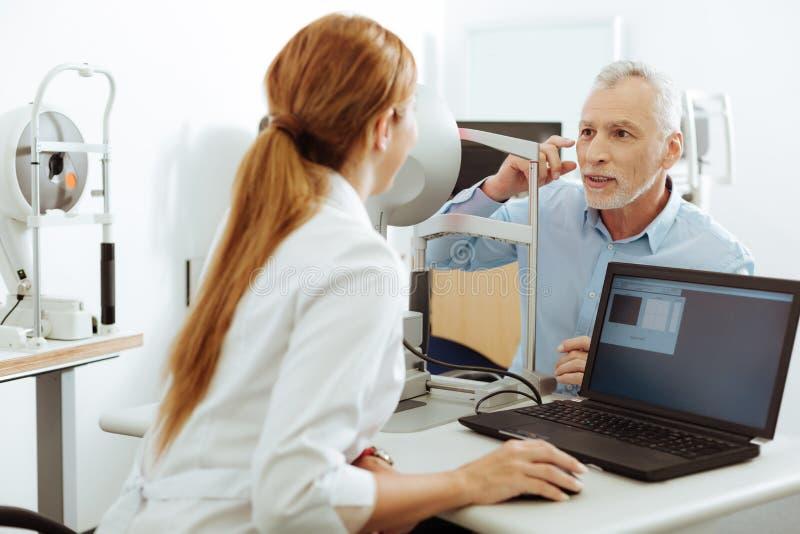 Den svartögda patienten som talar om, smärtar i hans öga för att manipulera royaltyfria foton