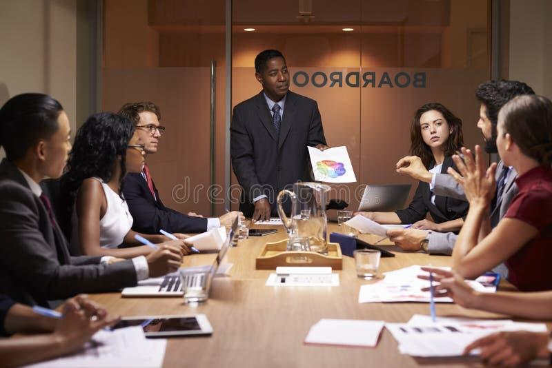 Den svarta affärsmannen står för att framlägga till kollegor på mötet royaltyfria bilder