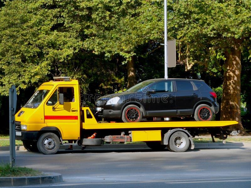 Den svarta bilen laddas på en gul bilbärgningsbil på en stadsgata arkivbild