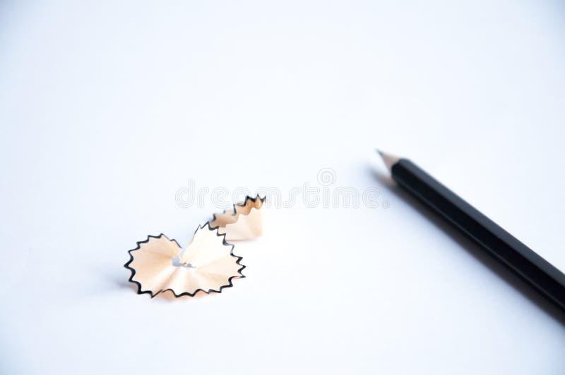 Den svarta blyertspennan ligger på tabellen Närliggande är shavings från en blyertspenna arkivfoton