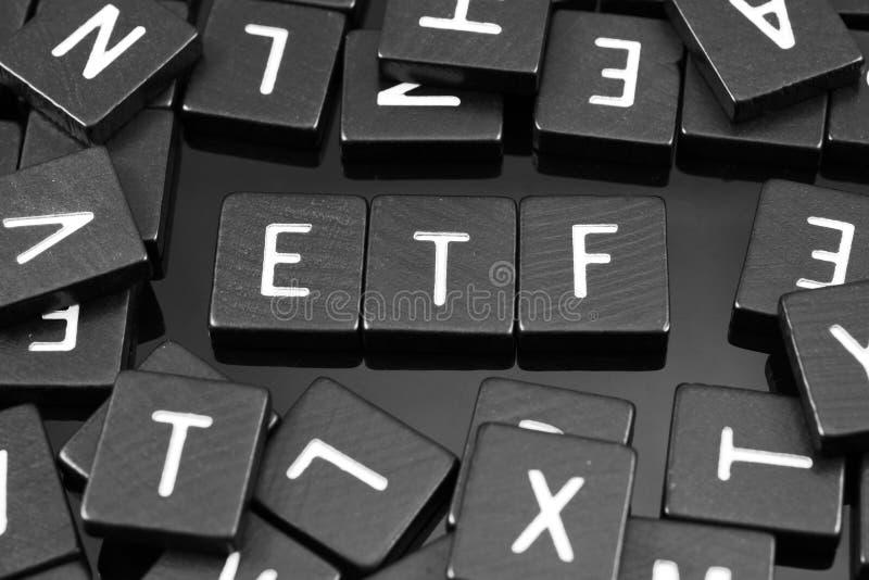 Den svarta bokstaven belägger med tegel att stava ordet & x22en; etf& x22; royaltyfri foto