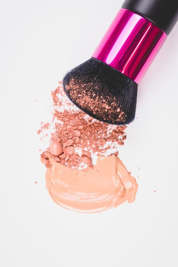 Den svarta borsten för utgör och krossade textur av beige framsidapulver och det beigea makeupsuddet av det krämiga fundamentet p royaltyfria foton