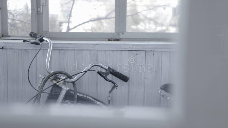Den svarta cykeln st?r p? gr? tr?balkong actinium Den snabba gamla cykeln st?r i st?ngd klar balkong med f?nster och royaltyfria foton