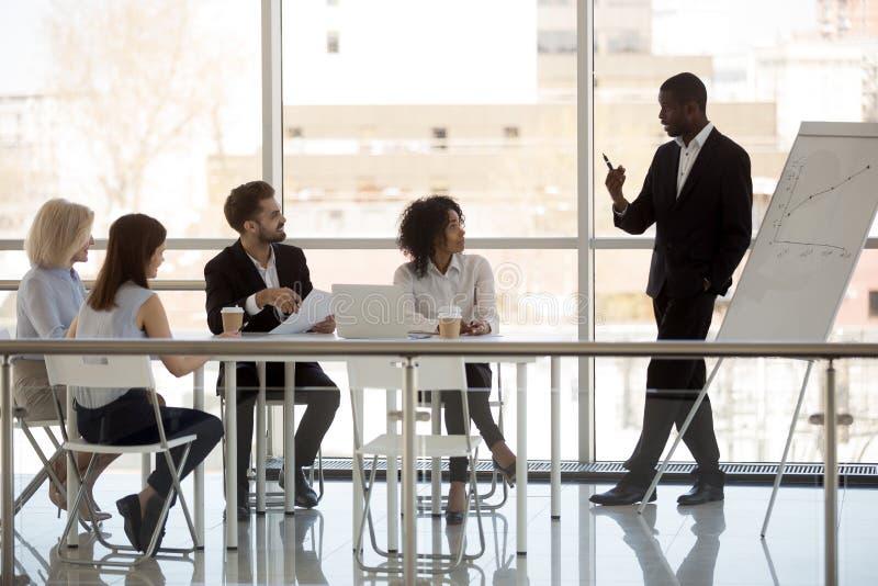 Den svarta företagaren gör presentation till arbetare under förhandsmöte royaltyfri bild