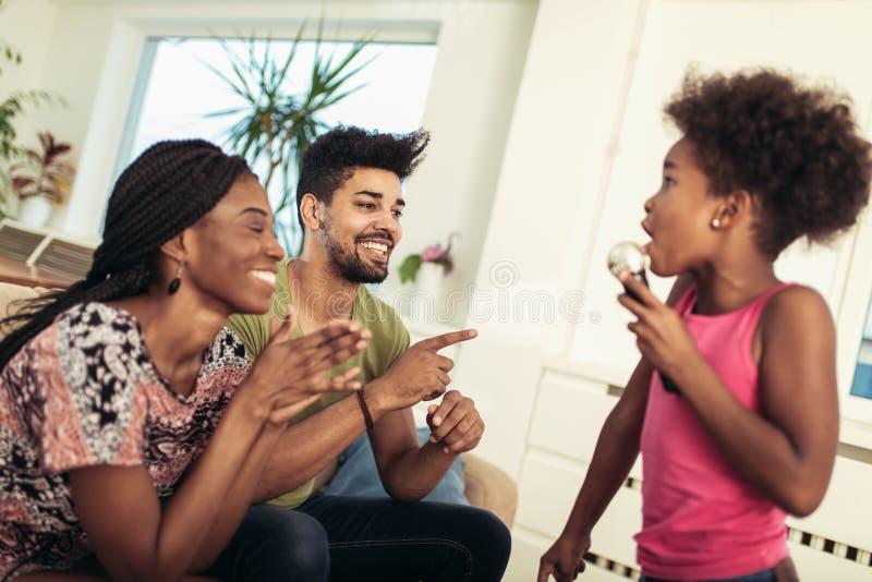 Den svarta familjen tycker om sjungande karaoke royaltyfri fotografi