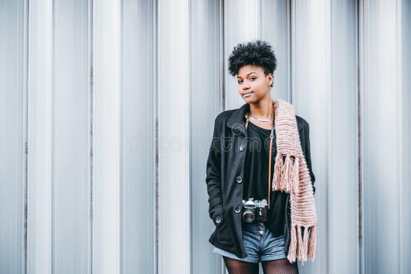 Den svarta flickan med tappningphotocamera nära mönstrade väggen royaltyfri bild