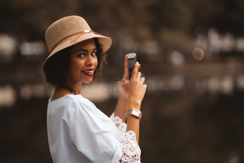 Den svarta flickan tar foto av dammet via smartphonen royaltyfria foton