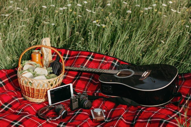 Den svarta gitarren och backet med smörgåsar, öl och frukter på röd picknick blancked Den lyckliga mannen tycker om på ferier på  arkivfoton