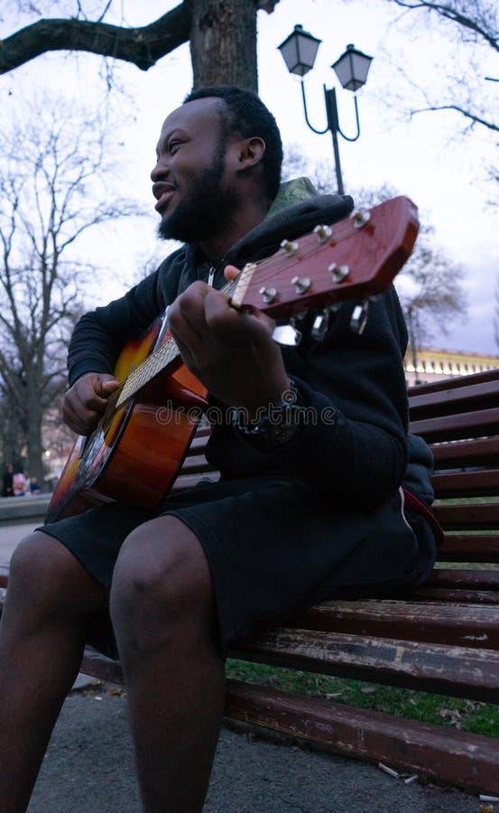 Den svarta grabben som spelar en gitarr och sjunger lyckligt sammanträde i en bänk av, parkerar arkivbild