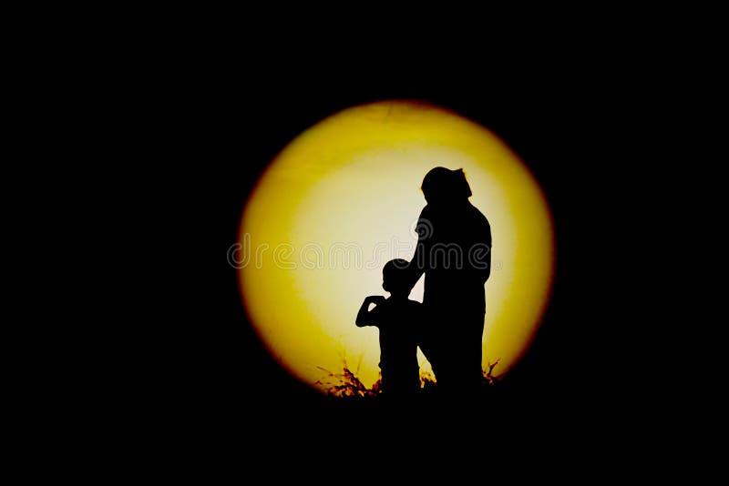 Den svarta konturn av mamman och ungar som håller ögonen på månen arkivfoto