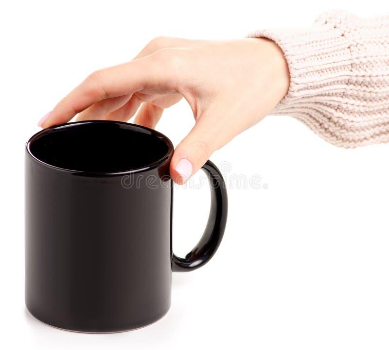 Den svarta koppen rånar i kvinnlig hand fotografering för bildbyråer