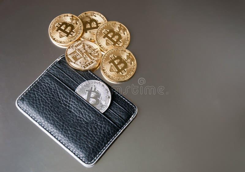 Den svarta läderplånboken på en mörk bakgrund med flera guld- och silverbitcoins som faller ut ur deras fack arkivbild