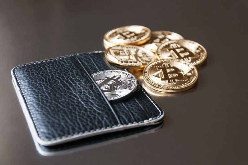 Den svarta läderplånboken på en mörk bakgrund med flera guld- och silvermynt av bitcoins som faller ut ur deras fack royaltyfri foto