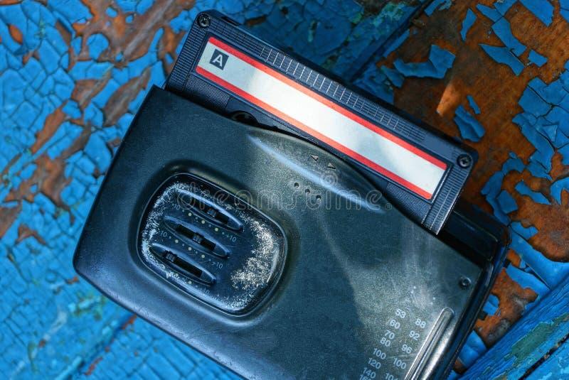 den svarta ljudsignal spelaren med en kassett ligger på en sliten blå tabell fotografering för bildbyråer