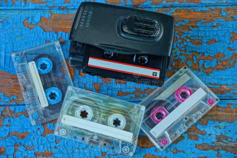 Den svarta ljudsignal spelaren med en kassett ligger på en sliten blå tabell arkivbild