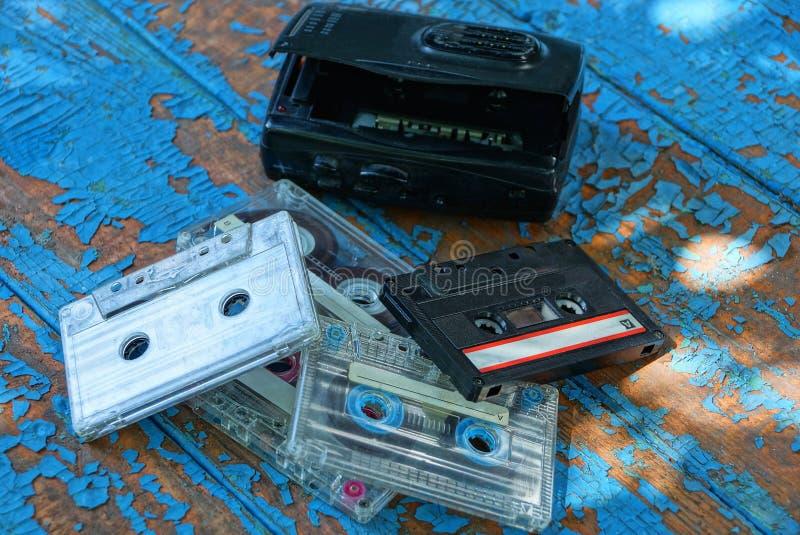 Den svarta ljudsignal spelaren med en kassett ligger på en sliten blå tabell arkivfoton