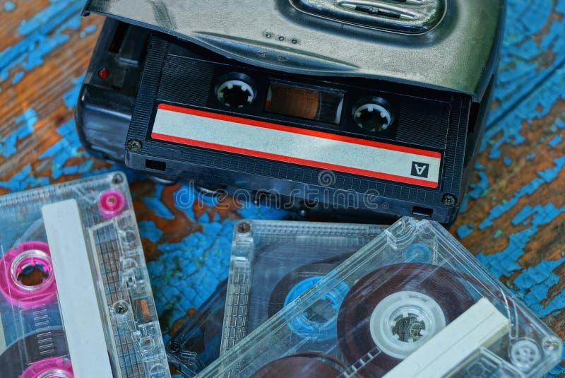 Den svarta ljudsignal spelaren med en kassett ligger på en sliten blå tabell royaltyfria bilder