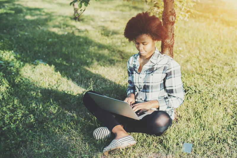 Den svarta lockiga flickan med bärbara datorn parkerar in royaltyfria bilder
