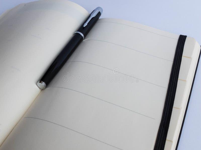 Den svarta metallaffärsreservoarpennan ligger inom den öppnade anteckningsboken med tomma sidor royaltyfri fotografi