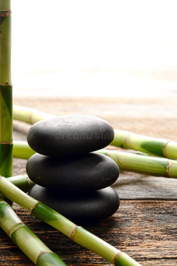 Den svarta polerade massagen stenar röset och Spa bambu arkivbilder