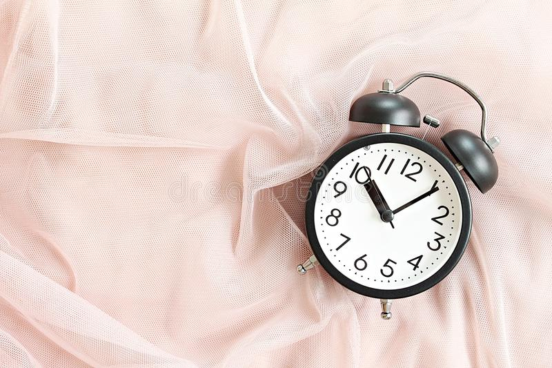 Den svarta retro ringklockan på säng i morgon, den bästa sikten eller lägenheten lägger med kopieringsutrymme som är klart för at royaltyfria foton