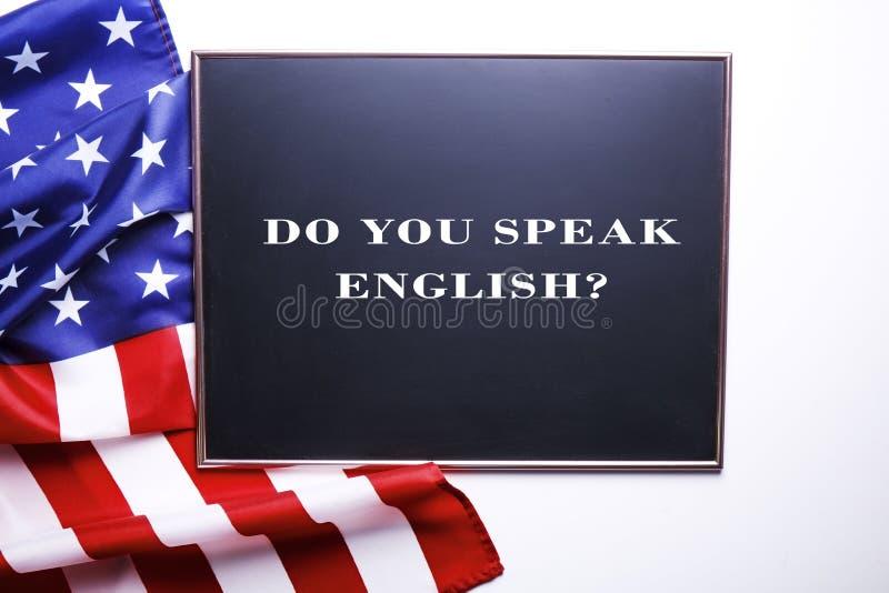 Den svarta svart tavlan med frågan talar du engelska? skriftligt i den och flaggan av Amerikas förenta stater arkivbild