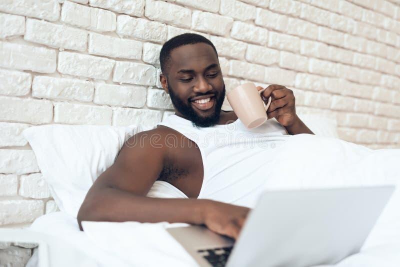Den svarta vakna mannen dricker kaffe i säng royaltyfria bilder