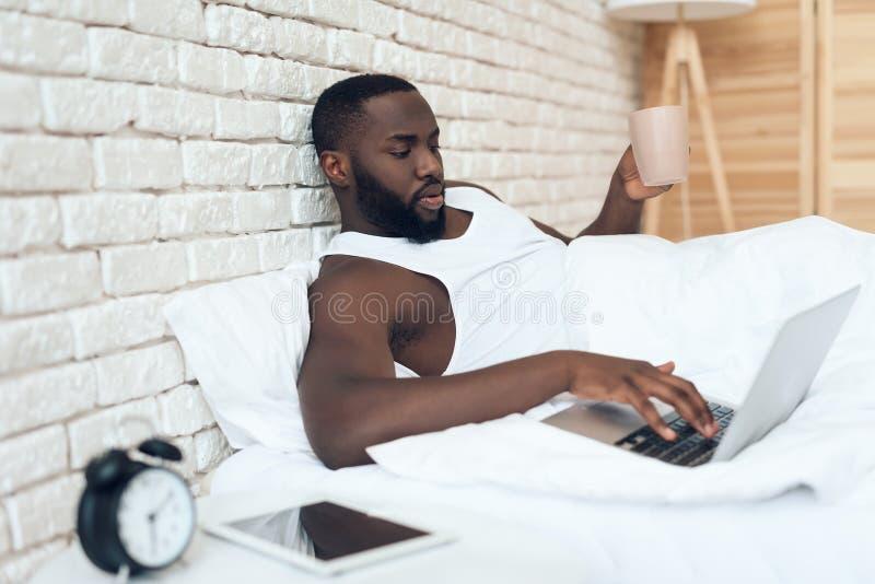 Den svarta vakna mannen dricker kaffe i säng royaltyfri bild