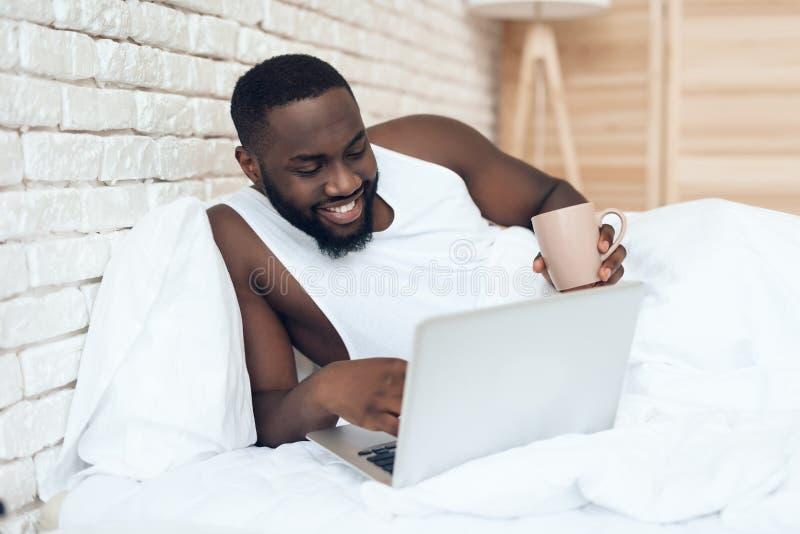 Den svarta vakna mannen dricker kaffe i säng royaltyfri fotografi