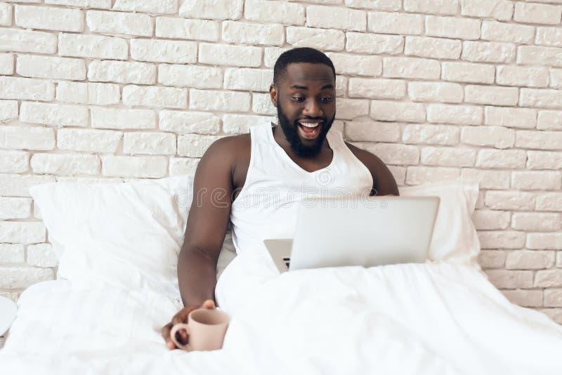 Den svarta vakna mannen dricker kaffe i säng royaltyfri foto