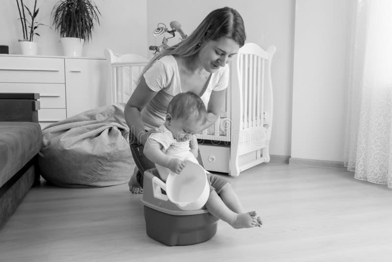 Den svartvita bilden av modern som sitter henne, behandla som ett barn på pottan arkivfoton