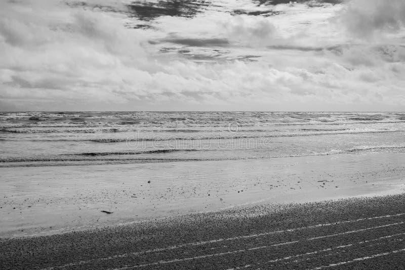 Den svartvita bildseascapesikten av sandstranden och havet vinkar bakgrund i regnig dag royaltyfria foton