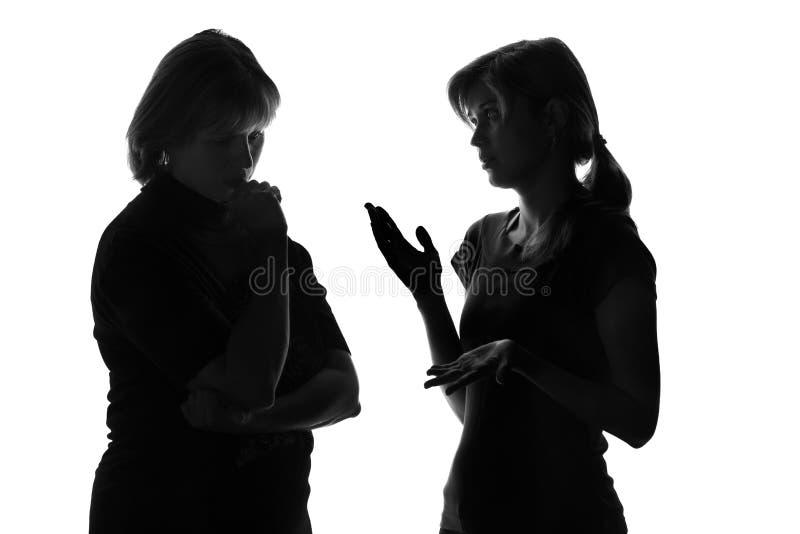 Den svartvita konturn av en moder oroade att hennes dotter lyssnar till problem i tonårstid arkivfoto