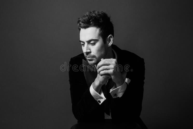 Den svartvita ståenden av en allvarlig ung stilig man i en dräkt, rubbning, räcker tillsammans arkivfoto