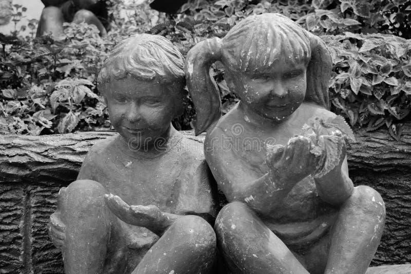 Den svartvita ståenden av en staty av två barn som ut når deras, gömma i handflatan royaltyfri bild
