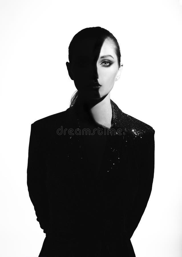 Den svartvita ståenden av den moderiktiga flickan med hår drog tillbaka och stilfull makeup i en glänsande klänning med en skugga arkivbild