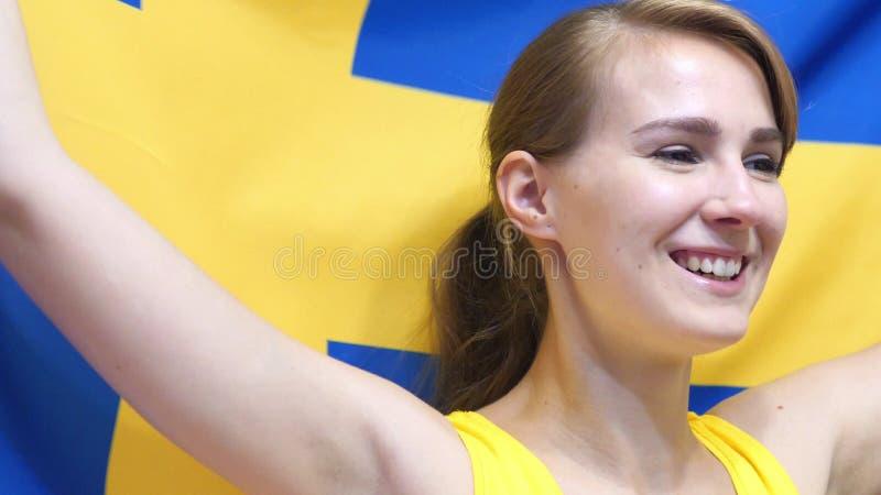 Den svenska unga kvinnan firar rymma flaggan av Sverige i ultrarapid arkivfoton