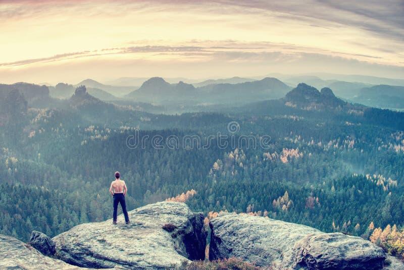 Den svettiga skjortan mindre löpare eller fotvandrare mot vitt vaggar och att se till den djupa dalen framme av honom arkivbilder