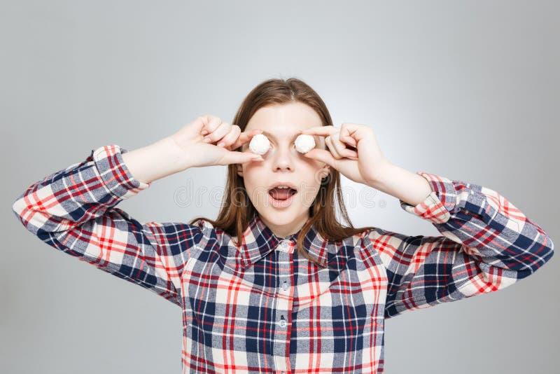 Den täckte gulliga skämtsamma tonårs- flickan synar med runda vita godisar arkivbilder